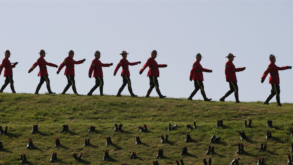 Royal Canadian Mounted Police officers marching past boots placed at the site