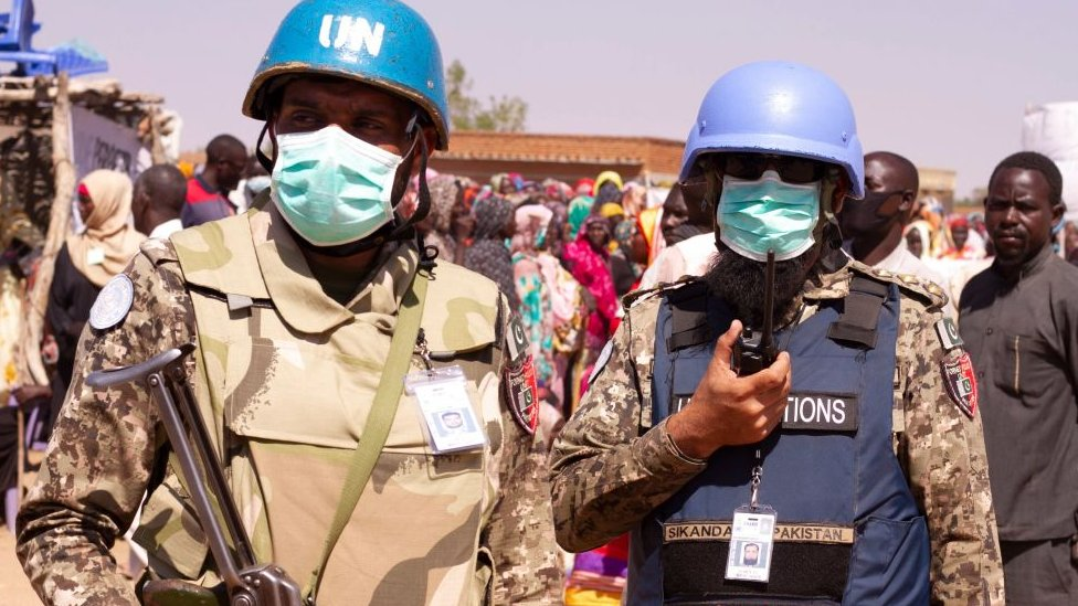 Members of the United Nations and African Union peacekeeping mission (UNAMID) look on as Sudanese internally displaced people stage a sit in to protest against the end of their mandate
