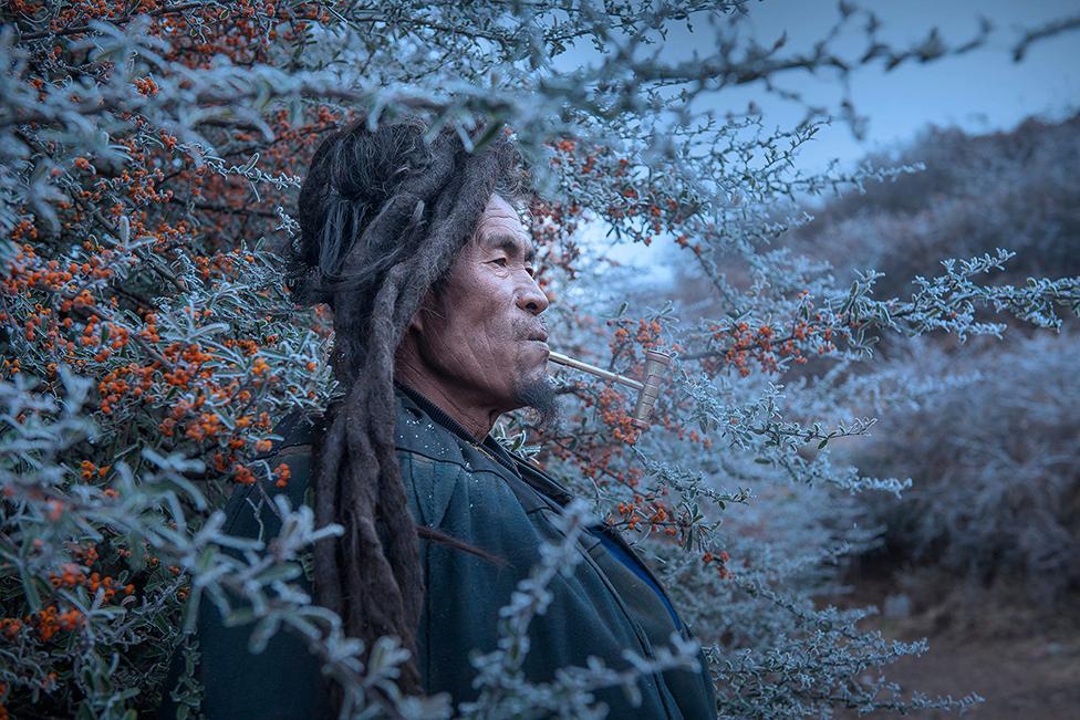 A pipe-smoking man in Liangshan Yi Autonomous Prefecture, China.