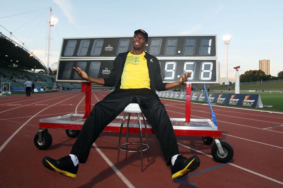 Usain Bolt frente a un cartel que muestra su récord de los 100 metros.