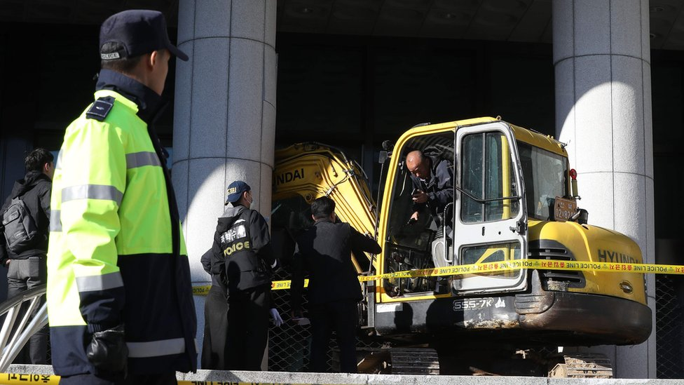 Policemen inspect an excavator after its driver attempted to ram the Seoul Central District Prosecutor's Office