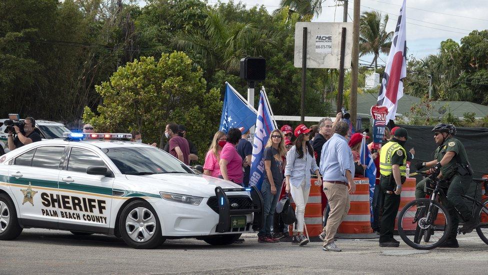Seguidores de Trump y un vehículo del sheriff del condado de Palm Beach