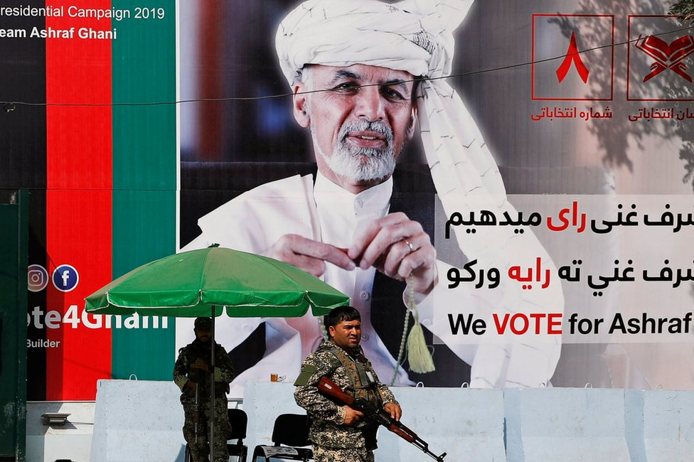 A member of the Afghan security force stands in front of a poster of Afghan presidential candidate Ashraf Ghani in Kabul, Afghanistan September 2, 2019