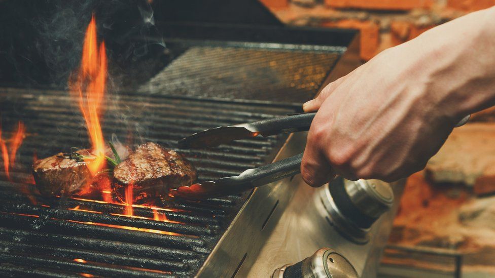 Close-up of a man cooking meat on a barbecue
