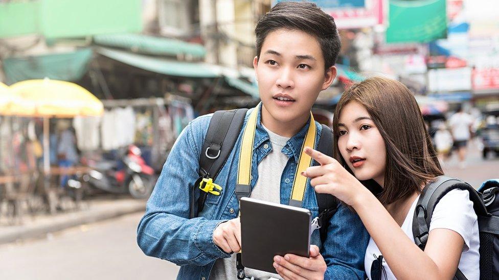 Una pareja joven asiática con una tableta intentando orientarse en la calle.