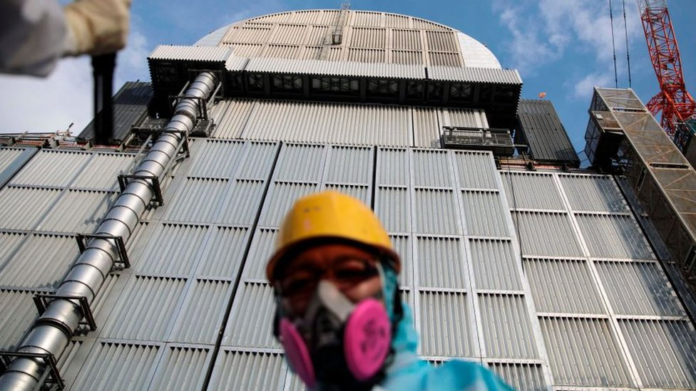 An employee of Tokyo Electric Power Company stands in front of the company's reactor number 3 at Fukushima Daichi nuclear power plant in Fukushima prefecture.