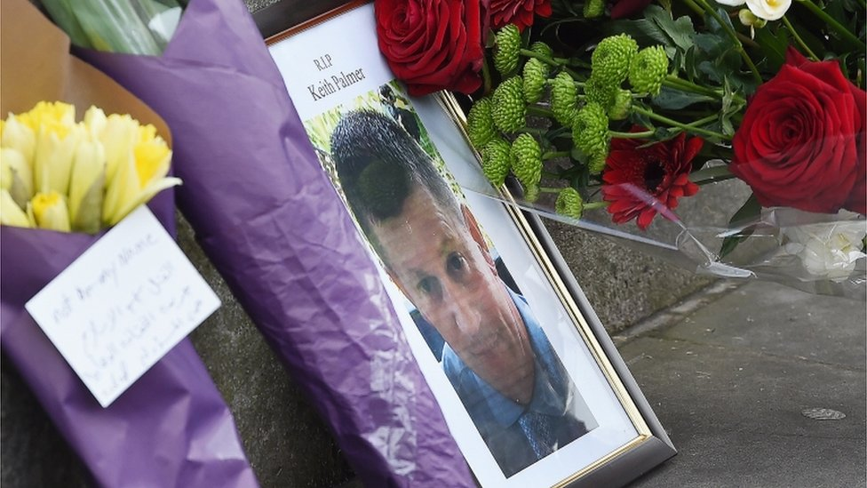 A photograph of policeman Keith Palmer who was killed in the terror attack is placed on Whitehall with flowers