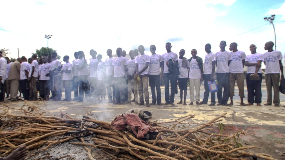 Militia fighters lined up in front of altar at the stadium in Kananga
