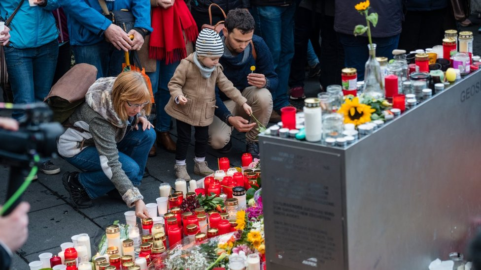 People mourn at the marketplace after yesterdays shooting on October 10, 2019 in Halle, Germany