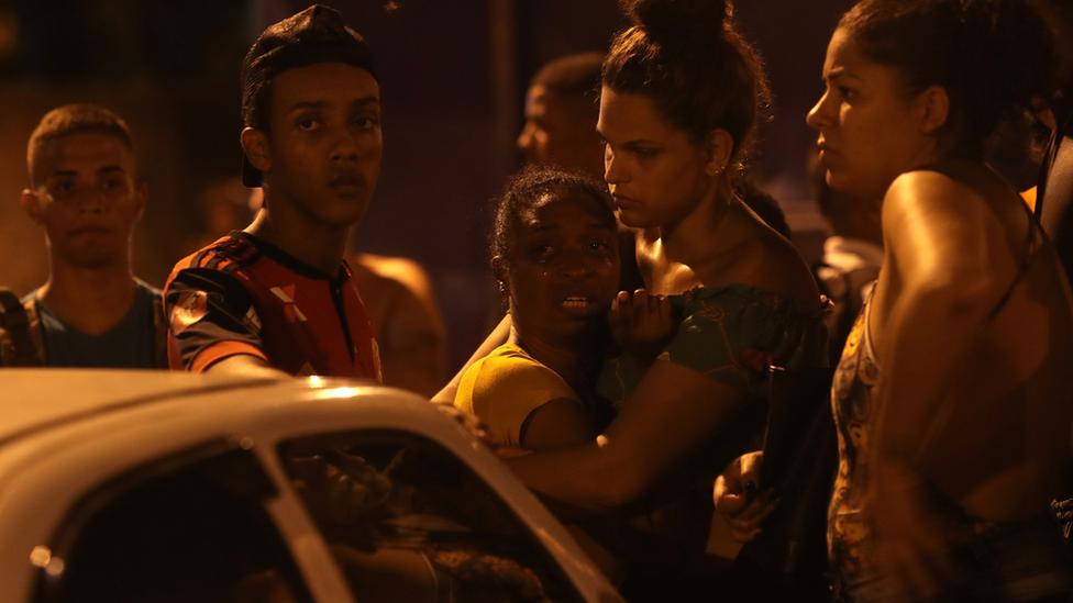 Personas reunidas lamentando la muerte de Jean Rodrigo da Silva.