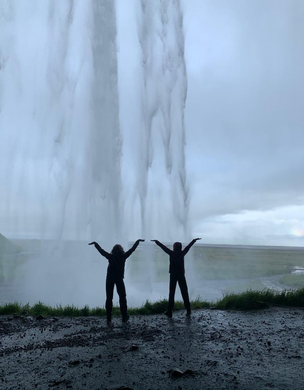 Two sisters pose as a waterfall pours in front of them