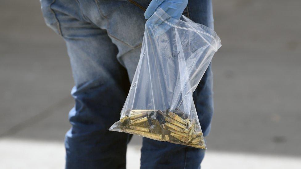 Una persona lleva una bolsa de plástico llena de balas
