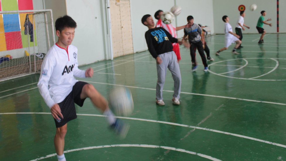 أوشيرو (يرتدي قميص مانشستر يونايتد الأبيض) خلال حصة في صالة الألعاب الرياضية بالمدرسة حيث تدرب بمفرده