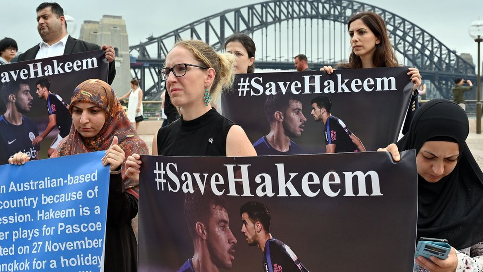 Protesters hold #SaveHakeem signs in front of the Sydney Harbour Bridge