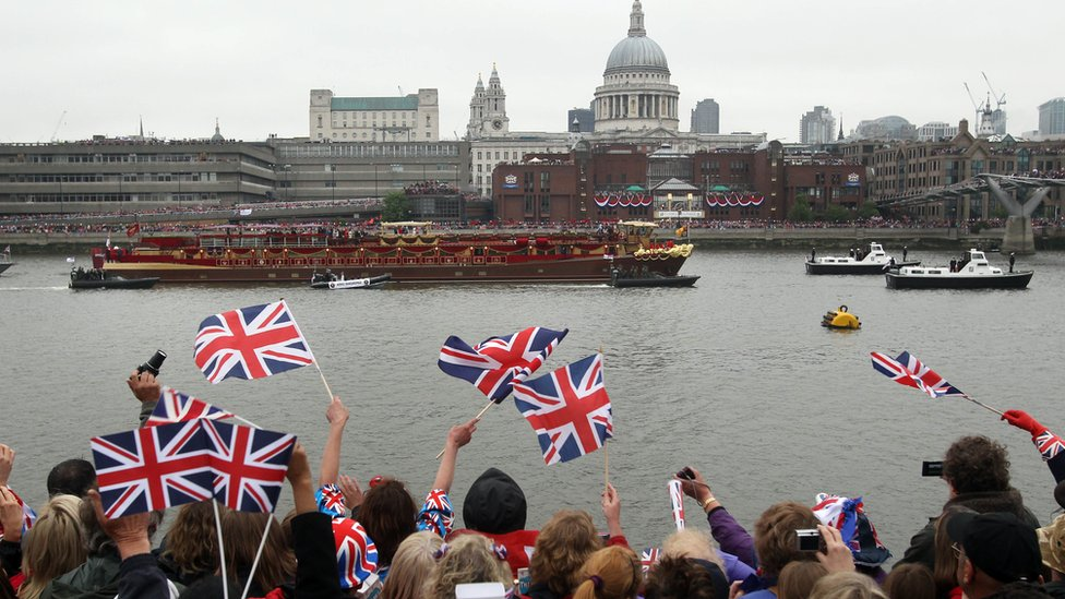 Onlookers cheer on the Queen's barge on the Thames