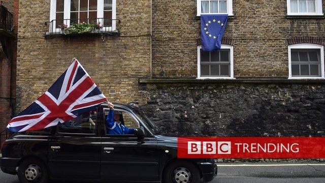 A black cab drives past an EU flag.
