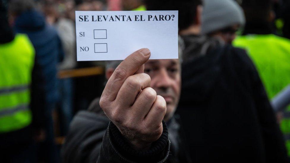 """Un manifestante con un papel que pregunta: """"Se levanta el paro?"""""""