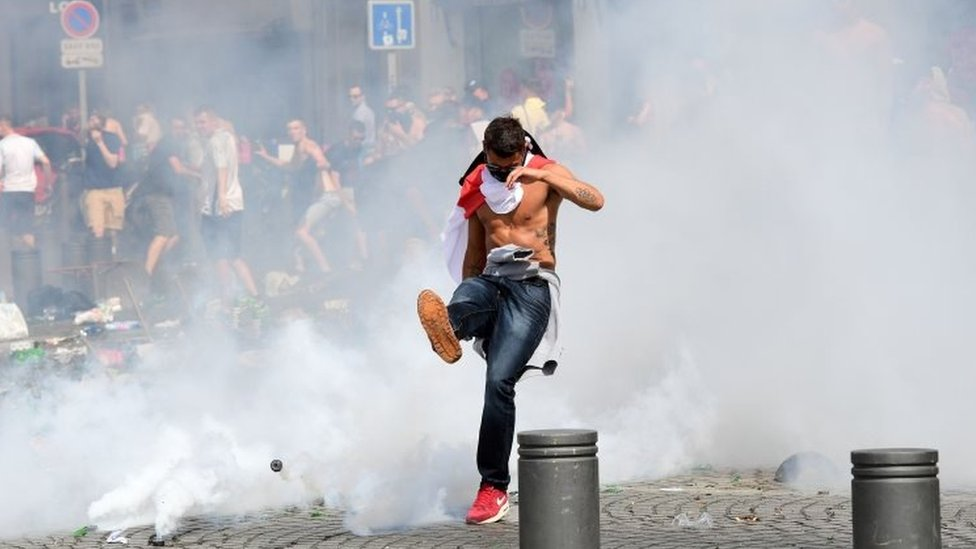 England fan kicks a can of tear gas away