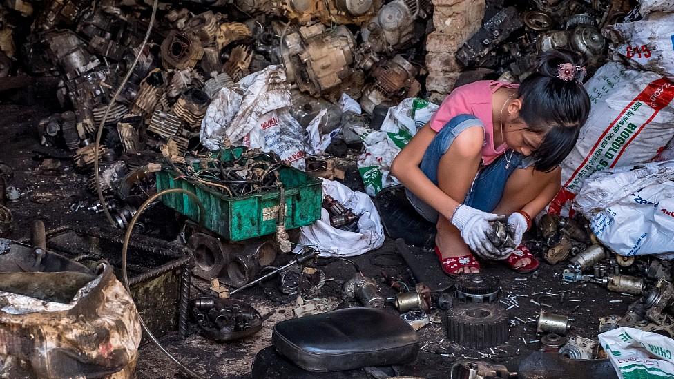 Adolescente reciclando componentes de baterías y otros desechos electrónicos en Vietnam