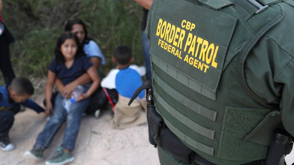 Central American asylum seekers wait as US Border Patrol agents take them into custody near McAllen, Texas, on 12 June 2018