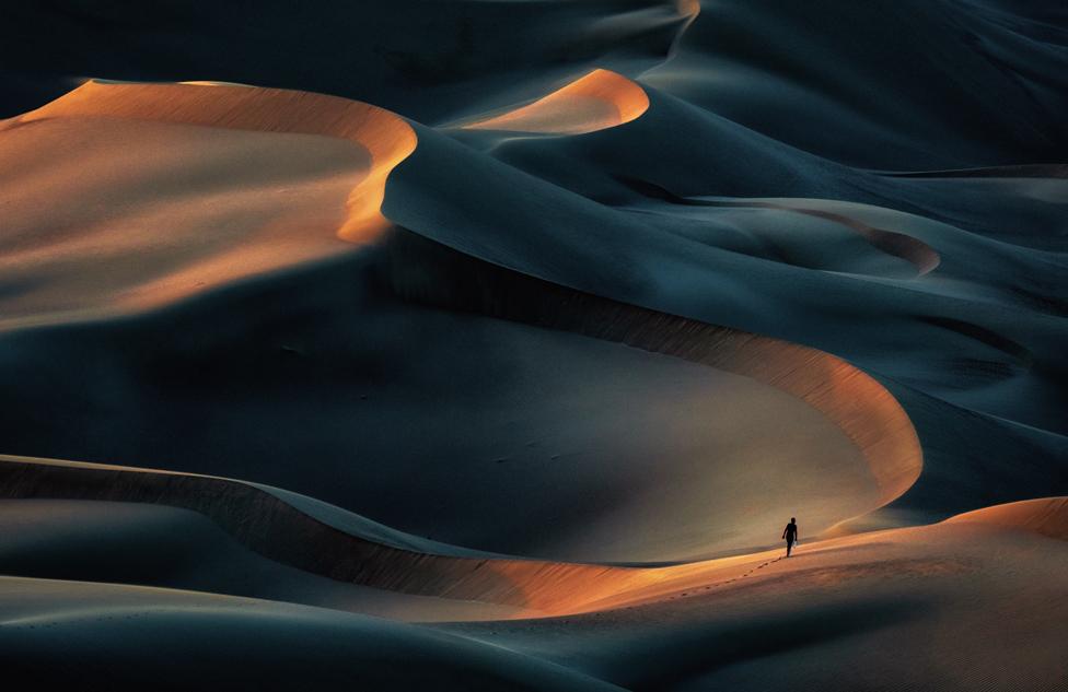 Distant figure walking across sand dunes