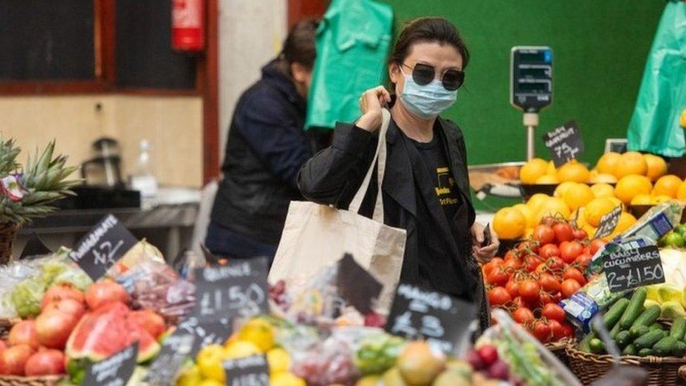 Seorang pengunjung mengenakan masker di Borough Market, London