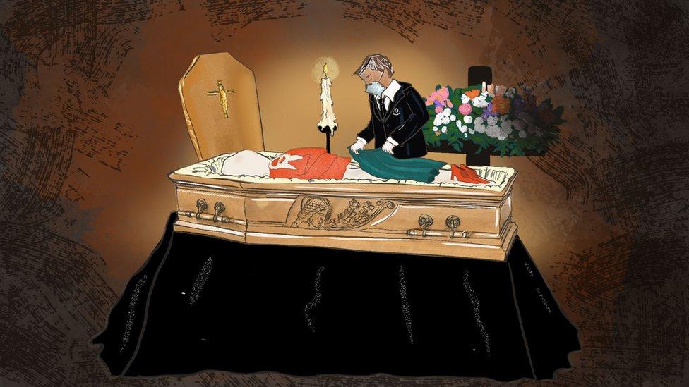 Un trabajadore de una empresa funeraria poniéndole ropa a un cadáver.