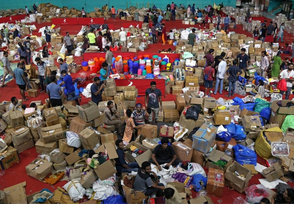 Volunteers organise boxes at an aid distribution centre at a stadium in Kochi, Kerala