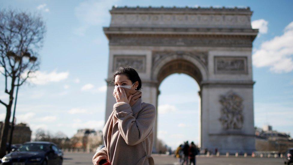 فتاة ترتدي قناعاً أثناء سيرها في أحد شوارع باريس