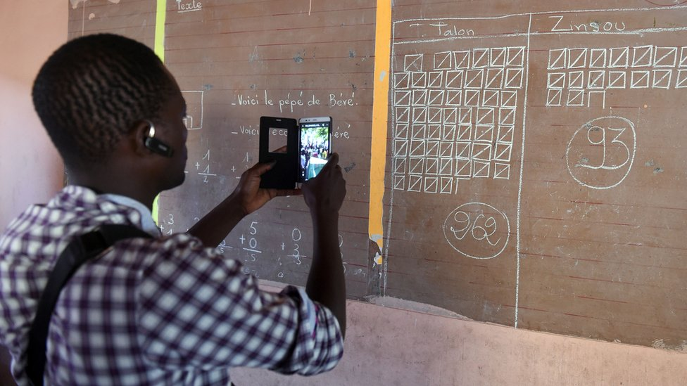 A man uses his phone to record the total votes cast in a polling station in Cotonou, Benin, 20 March 2016