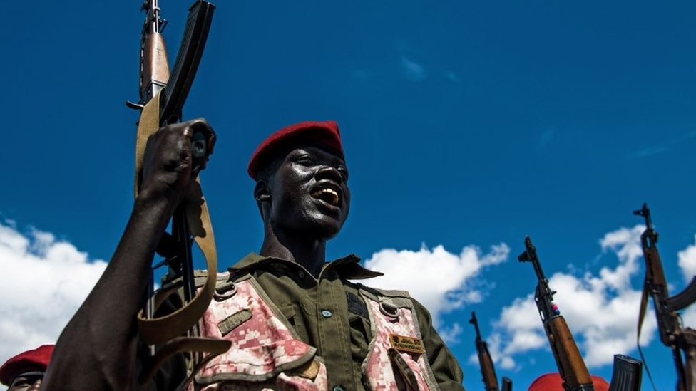 A Sudan People's Liberation Army (SPLA) soldier holds up a gun at a containment site outside Juba on April 14, 2016