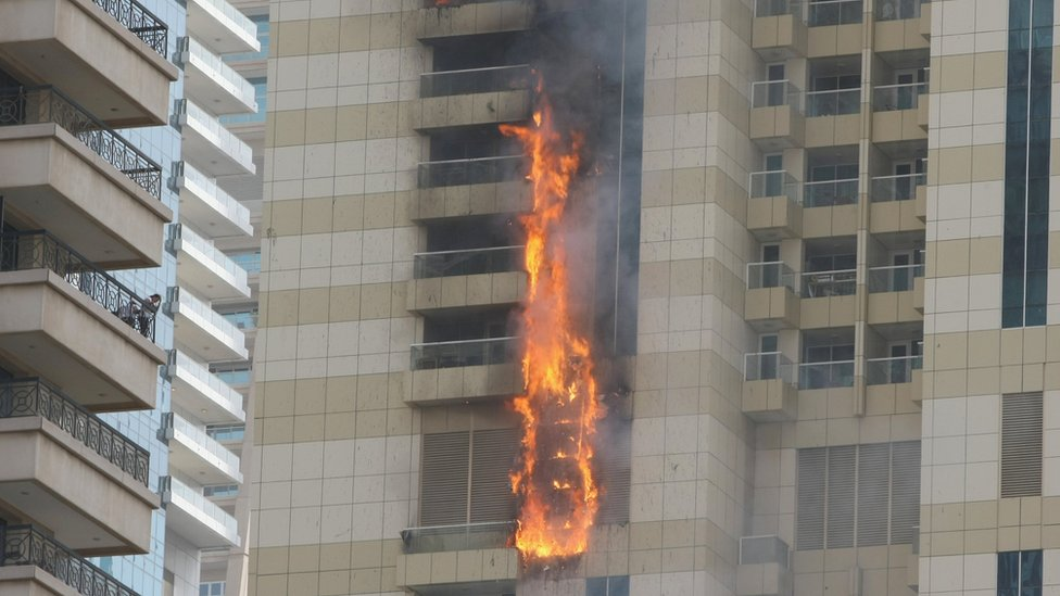Flames streak up the side of a skyscraper, 20 July 2016