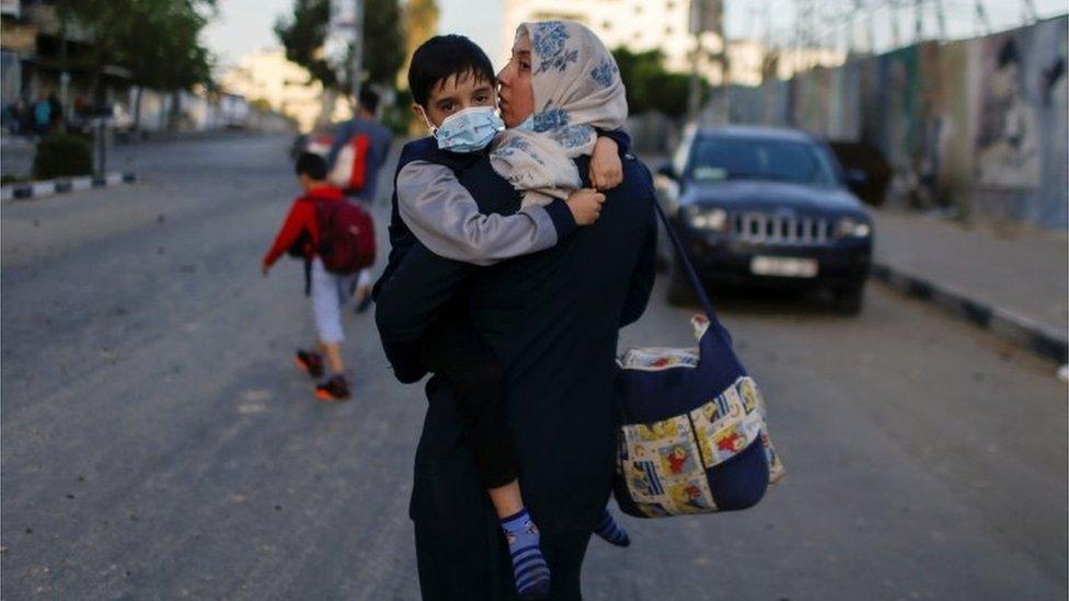 Una mujer palestina junto a su hijo evacúa su edificio después de que fuera impactado por un ataque aéreo israelita el 12 de mayo de 2021.