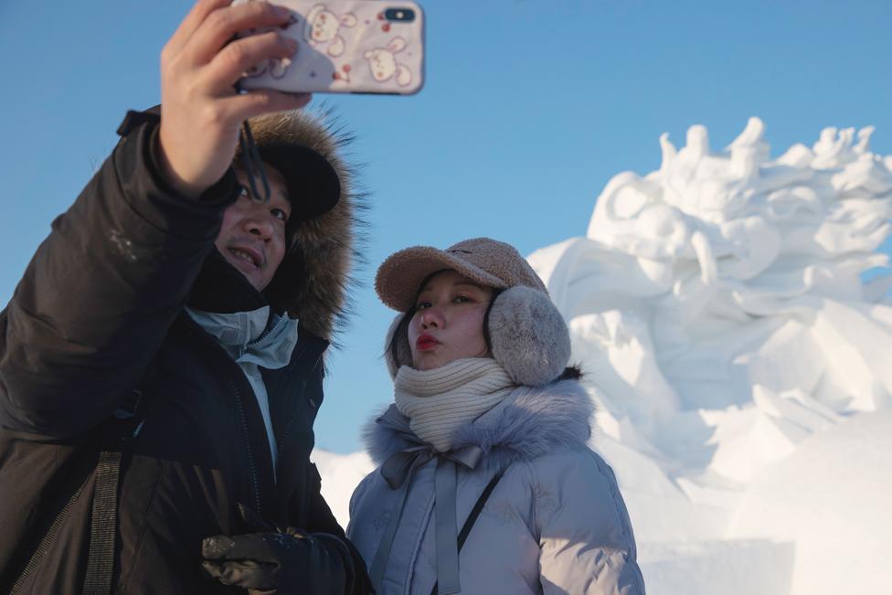 Dua orang berfoto selfie di depan patung salju