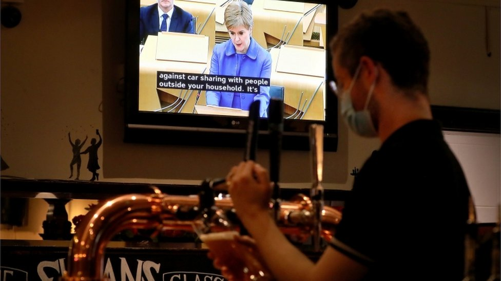 Bar staff in Sloan's in Glasgow watch First Minister Nicola Sturgeon making her statement