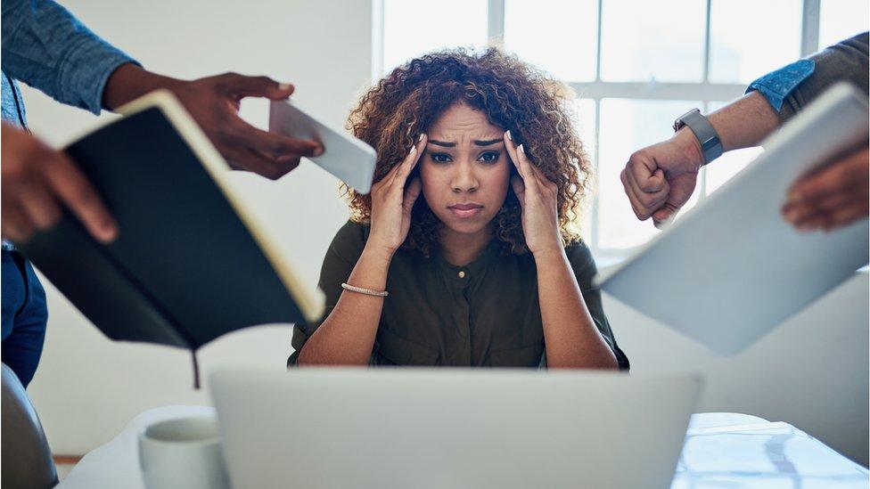 Imagen de una mujer que parece estar sobrecargada de trabajo.