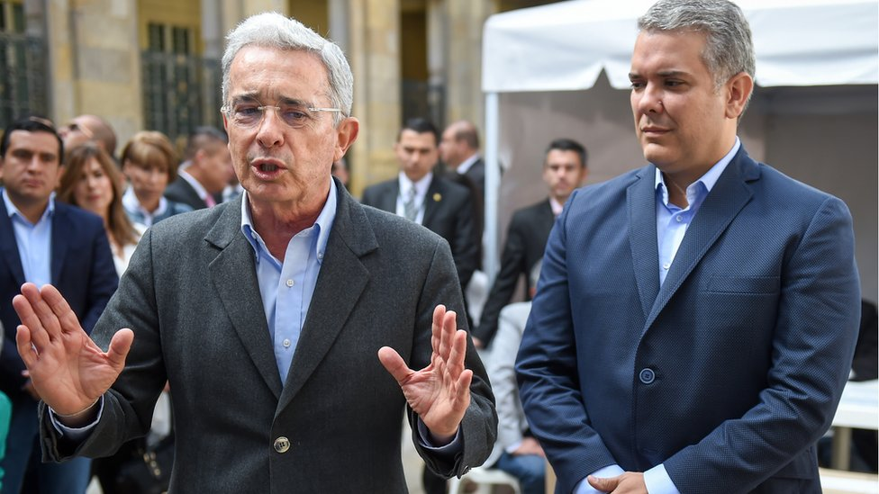 Alvaro Uribe (L) speaks to the press next to presidential candidate Ivan Duque, after casting his vote at a polling station during parliamentary elections in Colombia, in Bogota on March 11, 2018. C