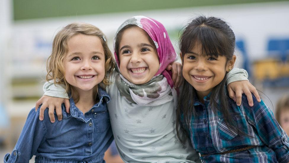 Niñas sonrientes - una blanca, otra con velo y otra asiática