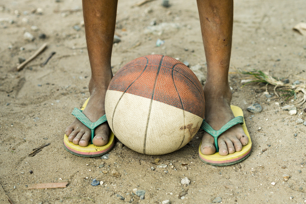 A basketball at a young man's feet