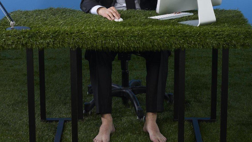 Hombre con pies descalzo en une escritorio con hierba artificial.