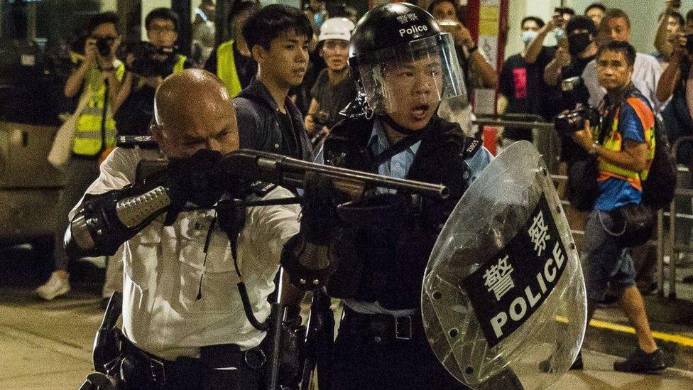 香港新界葵涌警署外一名警署警長(左)舉起雷鳴登霰彈槍指向示威者(30/7/2019)