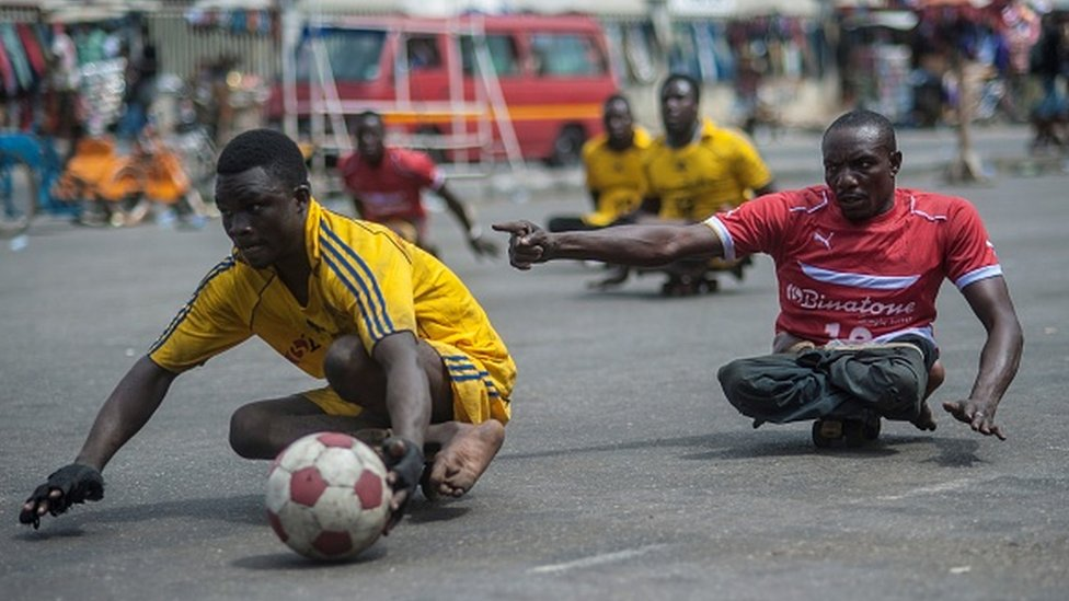 Hombres que fueron afectados con polio juegan con una pelota en Ghana.