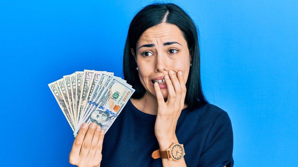 Mujer asustada con dinero