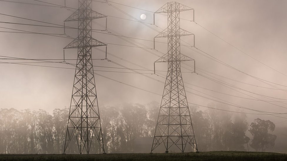 Power pylons shrouded in smoke with the sun behing