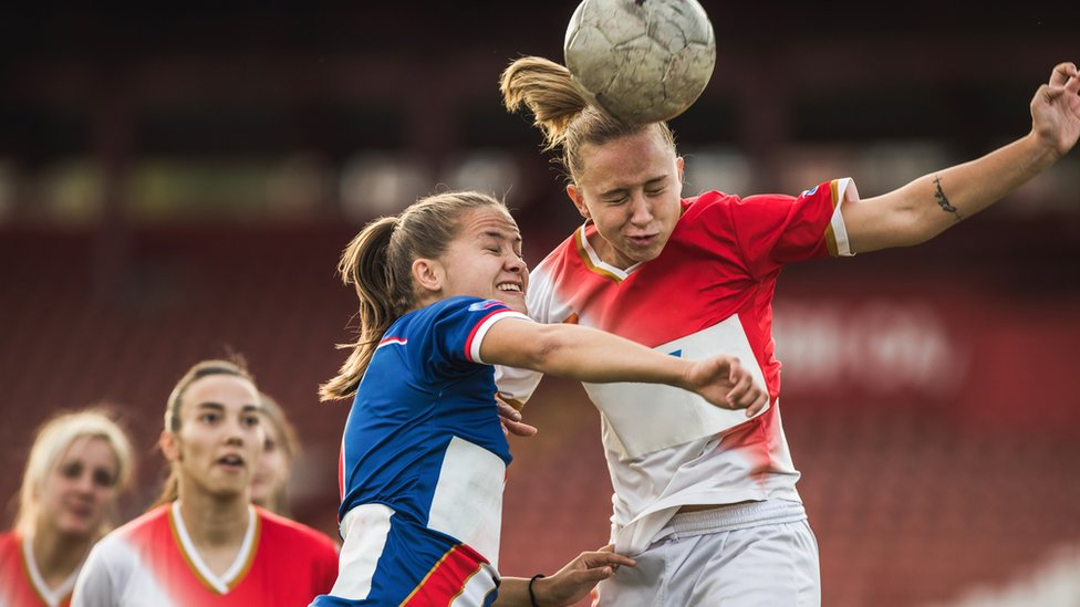 Female footballers heading the ball