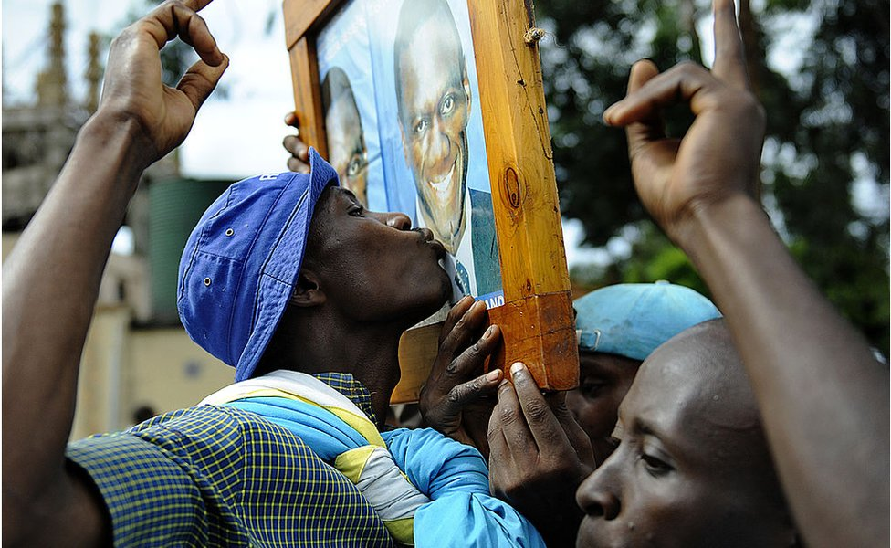 A suuporter kisses a portrait of Ugandan opposition leader Kizza Besigye during a welcome rally for Besigye in Kampala on 12 May 2011