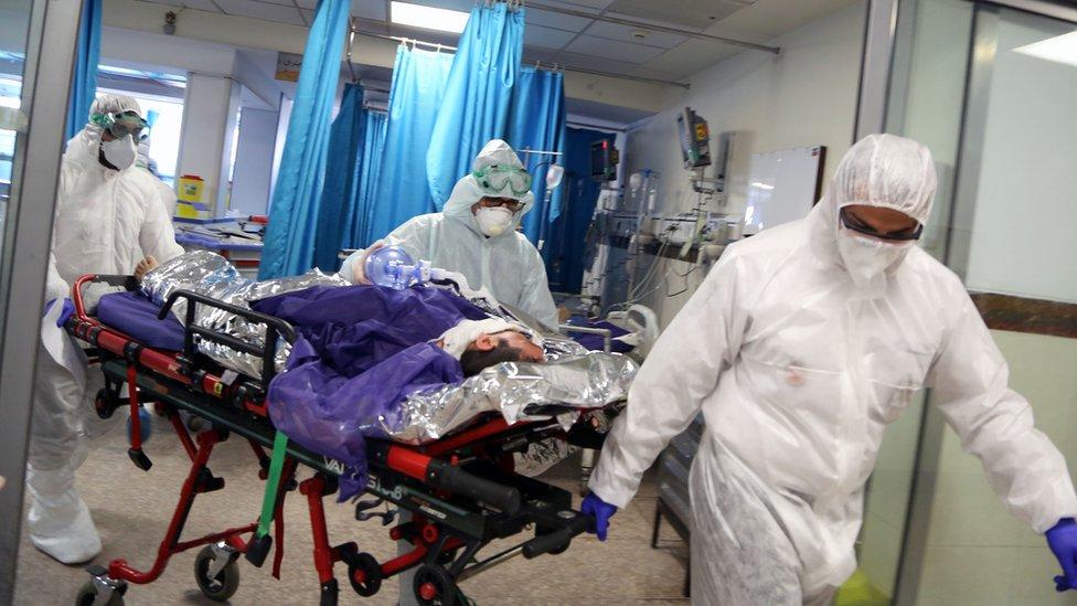 德黑蘭某醫院身穿全身保護服的救護員把一名病人推進醫院大廳(2/3/2020)