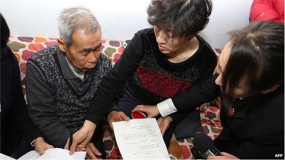 The judge of the higher people's court delivers retrial files to Hugjiltu's parents (C) in Hohhot, northern China's Inner Mongolia autonomous region on December 15, 2014