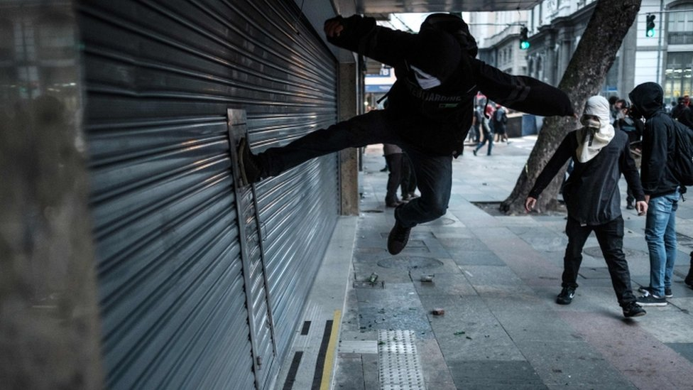 A protester kicks to break the shutter of a business along the street