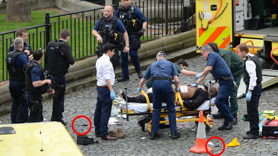 Emergency services at the scene while two knives lie on the ground outside the Palace of Westminster